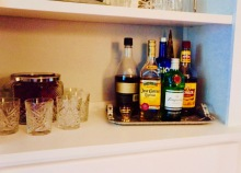 A friend uses a book shelf in her living room to create a well stocked bar